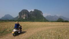 Tourist Couple Riding Motorcycle Through Countryside, Vang Vieng, Laos Stock Footage