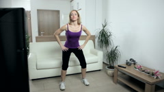 Woman exercising at home while watching instructions on TV. - stock footage