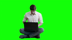 A man  working on a laptop while sitting on a background of a green scre - stock footage