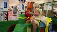 Little blonde child is happy sitting in toy railway Arkistovideo