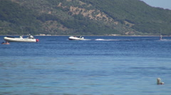 Ionian island harbor. Motor boat and a tourist water skiing. Holiday water sport Stock Footage