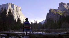 Stock Video Footage of Woman Stands By River In Yosemite National Park, And Looks In Awe At El Capitan