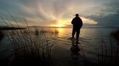 Video at Utah Lake during sunset with person wading in water. Stock Footage