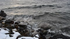 Incoming cold arctic wave bashing the snowy sea shore rocks - stock footage