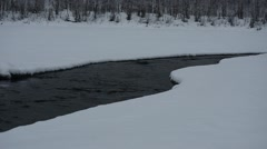 Cold flowing river water in winter through a hole in the river ice in norway Stock Footage