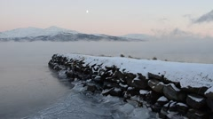 Rock pier ending in thick ice fog floating on the sea surface with snow mountain Stock Footage