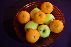 bowl of green apples and oranges - stock photo