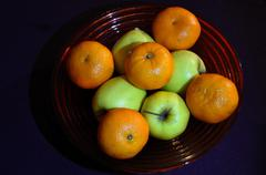 Bowl of green apples and oranges Stock Photos