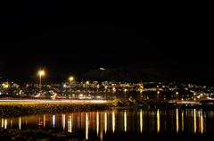 tromsoe city island at night with car traffic and light reflecting in fjord - stock photo