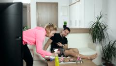 Woman cleaning the house and obstructing the man's view of the TV. Wide shot. - stock footage