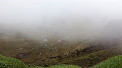 Mist blowing over rugged Andean scenery with cushion plant in foreground Stock Footage