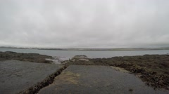 4K stone pier going out in the sea with seaweed all around it, grey clouded sky Stock Footage