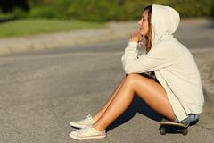 Profile of a pensive teenager girl sitting on a skate in the street - stock photo