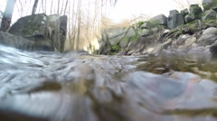 4K filming half above underwater stream with stone walls and forest surrounding Stock Footage