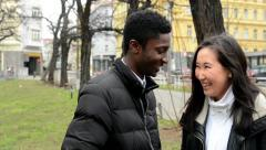 Happy couple laugh and talk (conversation) - urban street with cars in the city Stock Footage
