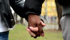 Young model couple in love - happy multicultural couple holding hands - street Stock Footage