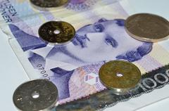 Norwegian crown coin currency on top of a one thousand paper bill macro photo Stock Photos