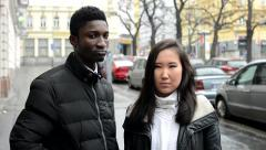 Unhappy couple disagree - black man and asian woman - urban street with cars - stock footage