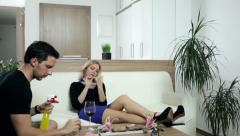 Man cleaning the house while woman is doing her nails. - stock footage