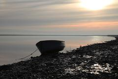 rowing boat anchored by the river at sunset - stock photo
