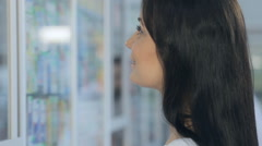 Young girl talking to pharmacist in drugstore - stock footage