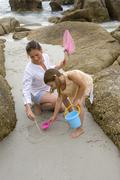 Mother and daughter drawing on sand. - stock photo