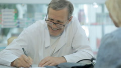 The doctor writes a prescription to the patient and communicates with her - stock footage