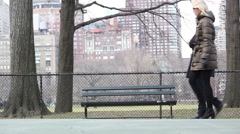 Two women walk in front of a park bench. - stock footage