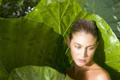 Woman in giant leaves Stock Photos