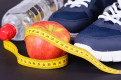 Fitness, weight loss concept with sneakers, apple & bottle - stock photo