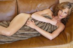 Nude woman on sofa - stock photo