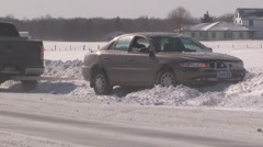Car in ditch and stuck on icy road in snow storm in cold winter 2015 Stock Footage