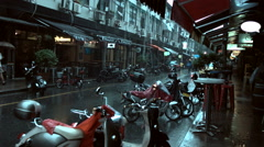 2 shots: Rainy YongKang rd Shanghai with people walking and parked scooters Stock Footage