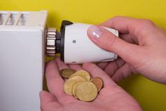 Radiator thermostat, coins and hand - yellow - stock photo