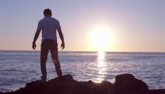 Man Explores Rocky Shoreline At Sunset In California Stock Footage