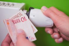Radiator thermostat, banknote and hand - green - stock photo