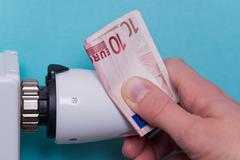 Radiator thermostat, banknote and hand - blue Stock Photos
