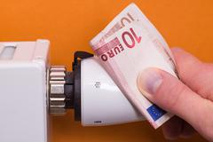 Radiator thermostat, banknote and hand - brown - stock photo
