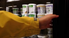 Woman selecting yogurt in grocery store Stock Footage
