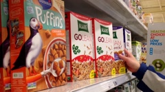 Pan shot of man selecting cereal in grocery store - stock footage