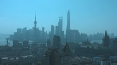 Pan up to sun to smoggy Shanghai skyline. - stock footage