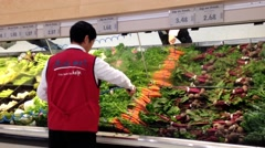 Man pouring water for fresh vegetables in grocery store Stock Footage
