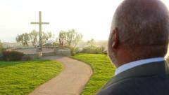 African American Male Looks over sunset with large wooden cross in distance Stock Footage