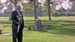Stock Video Footage of African American Middle Aged Male Standing With Flowers in Cemetary