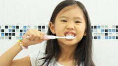 Little Asian child brushing her teeth - stock footage
