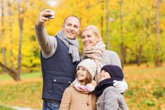 happy family with camera in autumn park - stock photo