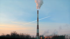 Smoke stacks and condensation trail of airplane Stock Footage