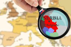 Magnifying glass over a map of Serbia - stock illustration