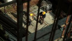 Stock Video Footage of Two construction workers tied rebar with wire at construction site. High angle.