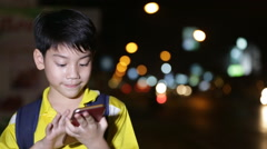 Little asian child playing with smart phone on night lights background Stock Footage